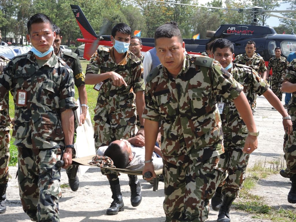 The Nepali military brings a man evacuated by helicopter in for treatment at the Nepali field hospital. The arrival of patients has slowed dramatically to a few dozen people per day by early May, compared with hundreds after the April 25, 21015 earthquake. (photo credit: Melanie Lidman / Times of Israel)