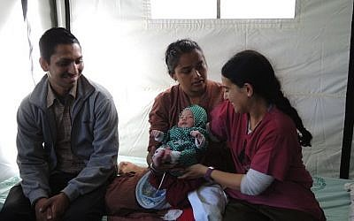 Israeli midwife Dganit Gery sits with Lata and Harendra Chang, whose baby was delivered at the IDF field hospital in Kathmandu on Friday, May 1, 2015. (Photo credit: Melanie Lidman)