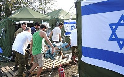 Israeli soldiers and doctors bring in an earthquake victim who arrived by jeep on Friday afternoon, May 1, 2015 (Photo credit: Melanie Lidman)
