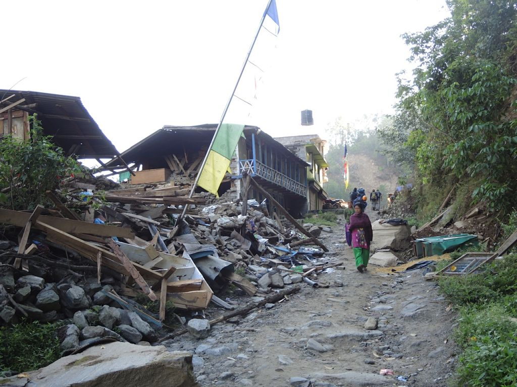 A woman walks beneath a strand of prayer flags in the demolished village of Topani, in the hard-hit Sidhulpalchowk district, seven hours away from Kathmandu, Nepal. May 2015. (photo credit: Melanie Lidman / Times of Israel)