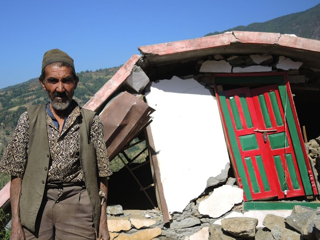 A man stands outside the ruins of his home a two hour walk from Topani, in the Sidhulpalchowk district, seven hours away from Kathmandu, Nepal. May 2015. (photo credit: Melanie Lidman / Times of Israel)