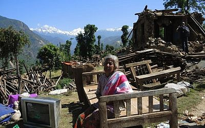 A woman sits with the salvaged items from her home in the village of Topani, Nepal. The villages had had electricity from a hydroelectric dam in the river, but it will likely be months before electricity can be restored to this area. May 2015. (photo credit: Melanie Lidman/Times of Israel)