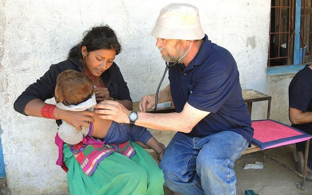 Dr. Asher Monser checks a reluctant toddler at the IsrAID mobile clinic in a village ten hours northeast of Kathmandu. (Photo credit: Melanie Lidman/Times of Israel)
