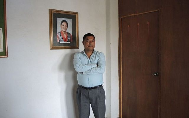 Bachchu N. Shrestha, the director of the Pasang Lhamu Sherpa Foundation and World Expeditions Trekking Company, stands next to a photo of Pasang Lhamu Sherpa, the first Nepali woman to summit Everest. Shrestha urges all Nepal lovers to come visit the country now, when it most needs the support of international tourists. (Melanie Lidman/Times of Israel)