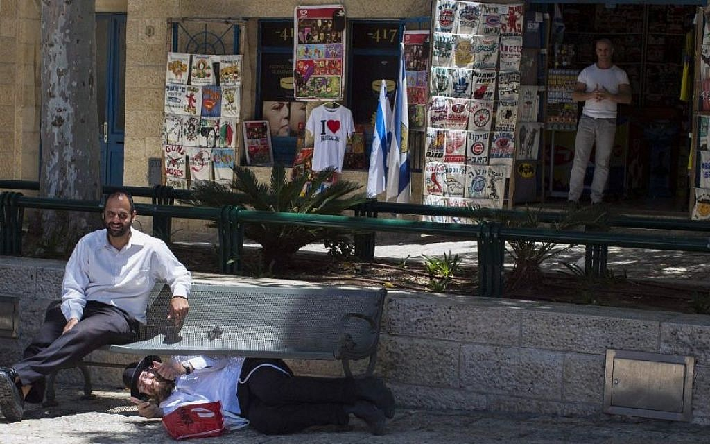 An Orthodox Jewish man hides under a bench as his friend sits and watches in the Jewish Quarter of Jerusalem as sirens are sounded throughout Israel as part of a IDF Home Front Command drill simulating a bomb attack on May 27, 2013. Sarah Schuman/ Flash90)