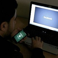 Illustrative image of a man in front of a computer with the Facebook logo, February 26, 2014 (Abed Rahim Khatib/Flash90)