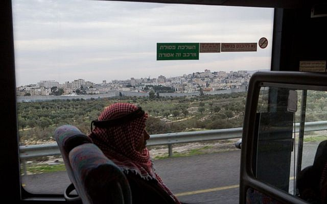 A Palestinian man rides the bus near the city of Bethlehem, December 18, 2014 (Miriam Alster/Flash90)