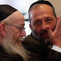Shas leader MK Aryeh Deri (right) speaks with United Torah Judaism leader MK Yaakov Litzman (left) during the opening session of the 20th Knesset, March 31, 2015. (Nati Shohat/Flash90)