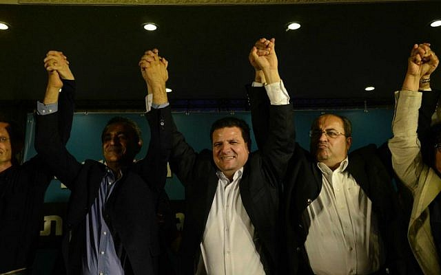 Arab Joint List head Ayman Odeh (center) reacts with other party members at the party headquarters in Nazareth as election exit polls are announced, March 17, 2015. (Basel Awidat/Flash90)