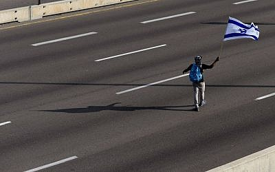 A lone flag-waver on the blocked Ayalon highway during a protest against violence and racism directed at Israelis of Ethiopian descent on May 03, 2015 (Photo credit: Ben Kelmer/FLASH90)