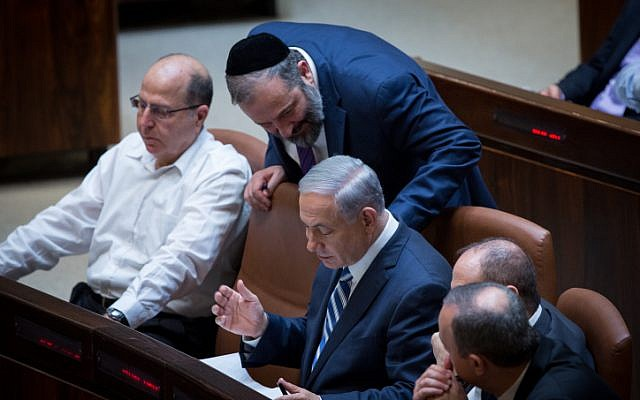 Prime Minister Benjamin Netanyahu speaks with leader of the Shas party, Aryeh Deri, during a plenum session in the Knesset on May 4, 2015. (photo credit: Miriam Alster/Flash90)