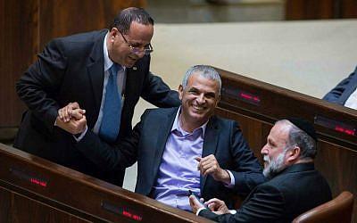 Kulanu party leader Moshe Kahlon (C) laughs with Likud's Ayoub Kara and Shas's Yitzhak Cohen in the Knesset plenum, May 4, 2015. (Miriam Alster/Flash90)