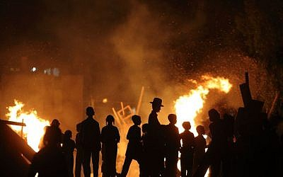 Ultra Orthodox Jews gather around a bonfire during celebrations of the Jewish holiday of Lag B'Omer in Bnei Brak on May 06, 2015. (photo credit: Yaakov Naumi/Flash90)