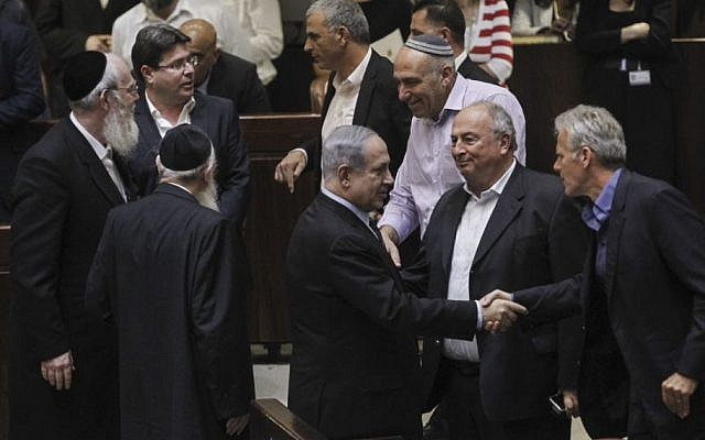 Prime Minister Benjamin Netanyahu (center) seen with other members of Knesset, after a Knesset vote on enabling an increase in the number of government ministers, May 11, 2015. (photo credit: Miriam Alster/Flash90)