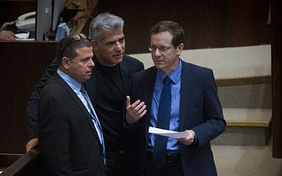 Zionist Union leader Isaac Herzog speaks with Yesh Atid party leader Yair Lapid and Zionist Union MK Eitan Cabel during a plenum session on expanding the number of ministers in the new cabinet, on May 11, 2015. (Photo credit: Miriam Alster/Flash90)