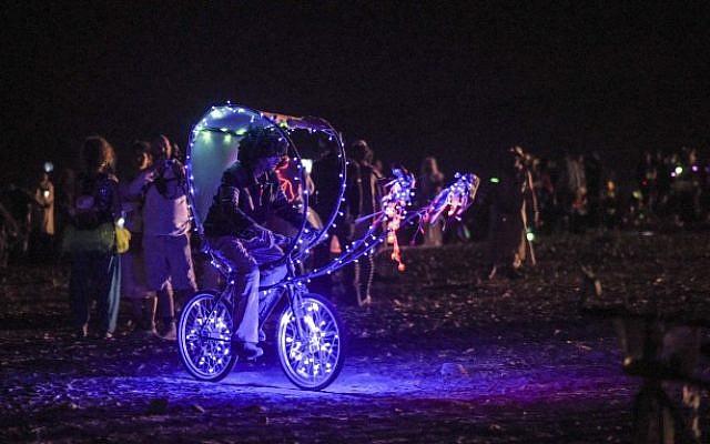 An art bike rides through the 67 art installations scattered across the Midburn Festival from May 20-24.  (Ben Kelmer/Flash90)