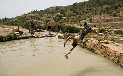 Jewish and Arab men enjoy a refreshing swim in a mountain spring near Jerusalem on May 27, 2015. (Yonatan Sindel/Flash90)