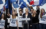 France's far-right National Front president Marine Le Pen, center, surrounded by supporters, sings the French National Anthem after her speech at Opera Plaza during the annual May Day march, in Paris, May 1, 2015. (photo credit: AP Photo/Francois Mori)