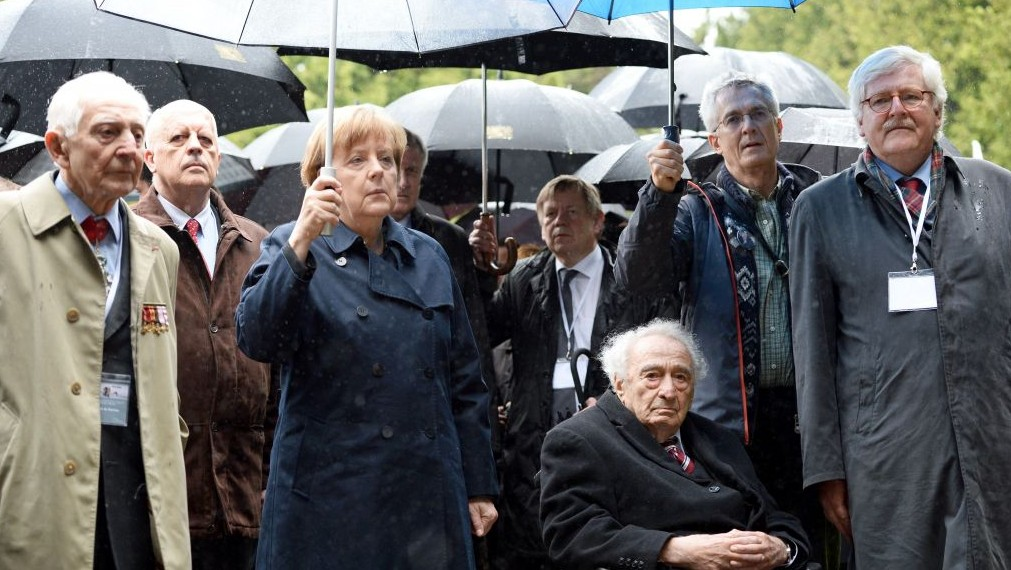 German Chancellor Angela Merkel, third left, and camp survivor Max Mannheimer, fourth from left in wheel chair, lay a wreath at the crematory of the former Nazi concentration camp in Dachau, southern Germany, May 3, 2015. (photo credit: Andreas Gebert/AP)