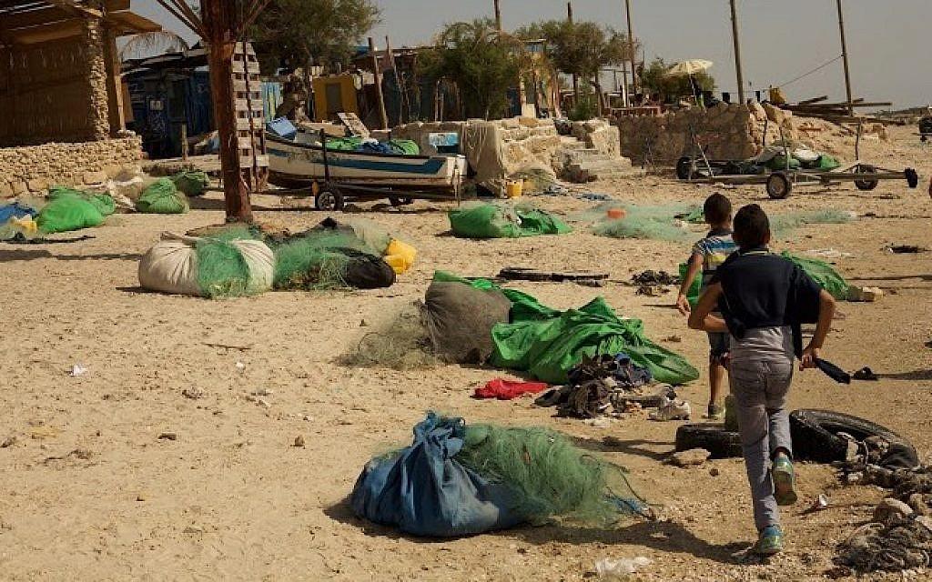 Children run through fishermen's nets on the beach at Jisr az-Zarqa (Eliyahu Kamisher)
