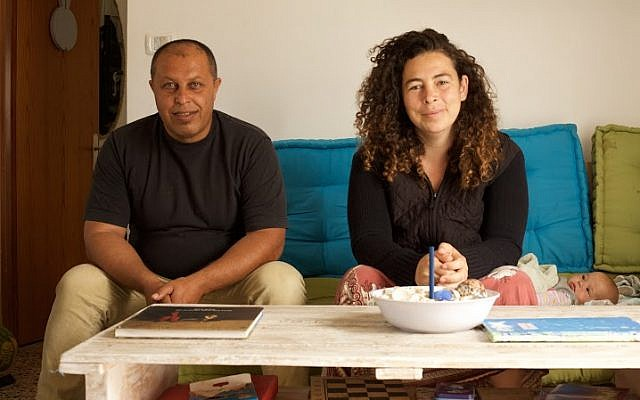 Ahamad Juha (left) and Neta Hanien, co-owners of Juha's Guesthouse, sit in the main room of the hostel. (Eliyahu Kamisher)