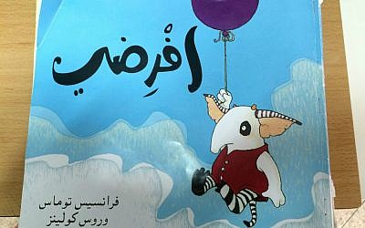 """Arabic edition of """"Supposing,"""" written by Frances Thomas and Illustrated by Ross Collins, one of the Maktabat al-Fanoos (Lantern Library) books. (photo credit: Renee Ghert-Zand/Times of Israel staff)"""