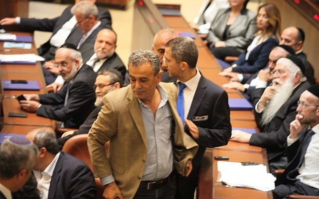 MK Jamal Zahalka is removed from the Knesset plenum after making repeated catcalls during a speech by Prime Minister Benjamin Netanyahu on Thursday, May 14, 2015 (Knesset spokesperson)