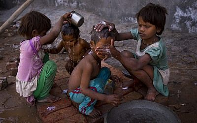 Two young girls bathe their siblings by a public tap on a hot summer day at Badshahpur, on the outskirts of New Delhi, India, Wednesday, May 27, 2015. Delhi recorded a maximum temperature of 42 degrees Celsius on Wednesday. In southern India, hundreds of people have died since the middle of April as soaring summer temperatures scorch the country, officials said Tuesday. (AP Photo/Saurabh Das)