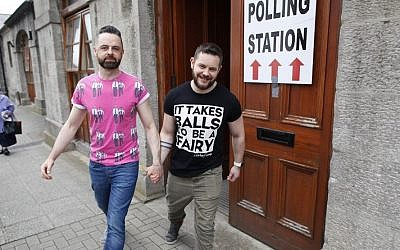 Partners Adrian, center left and Shane, leave a polling station after casting their vote in Drogheda, Ireland, Friday, May 22, 2015. (AP/Peter Morrison)