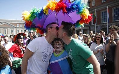 Two men kiss as first results start to filter through in the referendum, Dublin, Ireland, Saturday, May 23, 2015. Ireland voted resoundingly to legalize gay marriage. (AP Photo/Peter Morrison)