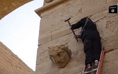 In this image made from a video posted on YouTube on April 3, 2015, a militant hammers away at a face on a wall in Hatra, a large fortified Iraqi city recognized as a UNESCO World Heritage Site. (AP, File)