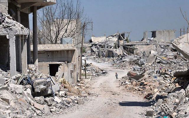 In this picture taken on Saturday, April 18, 2015, a Kurdish boy, center background, walks between buildings that were destroyed during the battle between the US backed Kurdish forces and the Islamic State fighters, in Kobani, north Syria. (Photo credit: AP/Mehmet Shakir)