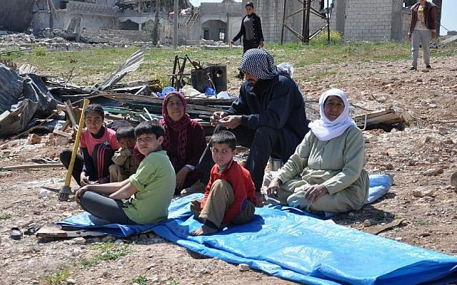 File: In this picture taken on Saturday April 18, 2015, a displaced Kurdish family sit in the open air field near their house which was destroyed during the battle between the US backed Kurdish forces and the Islamic State fighters, in Kobani, north Syria. (AP/Mehmet Shakir)