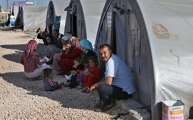 In this picture taken on Monday, April 20, 2015, Kurdish refugees sit outside their tents at the Arin Mirxan refugee camp, in Suruc town, Turkey. (AP/Hussein Malla)