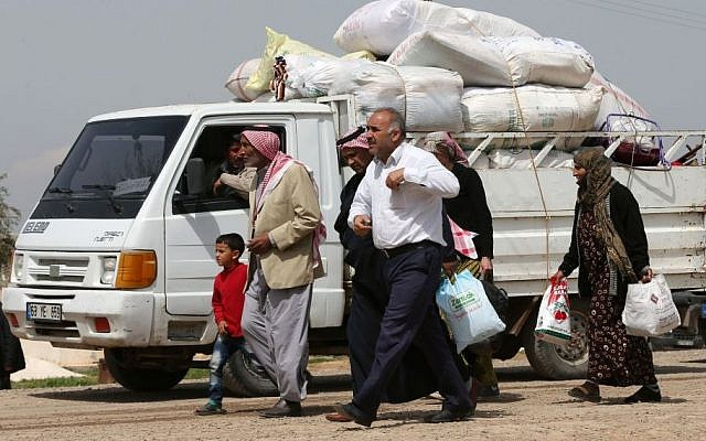 In this picture taken on Monday April 20, 2015, Kurdish refugees who fled from Kobani walk next to a pickup truck full of their belongings on their way to a border gate to return to their town, at the Mursitpinar border crossing in Suruc town, Turkey. (Photo credit: AP/Hussein Malla)