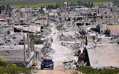 A car passes through Kobani, north Syria on April 18, 2015. The area was destroyed during the battle between the US-backed Kurdish forces and the Islamic State fighters. (Mehmet Shakir/AP)
