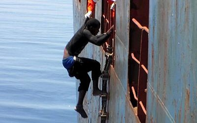 Dramatic footage emerged Tuesday May 5, 2015, filmed by a crew member, showing a Mediterranean Sea rescue of migrants on a sinking rubber boat desperately clambering up ropes and a ladder from the cargo ship Zeran that came to their aid on May 3, 2015, in the sea between Libya and Sicily. Five bodies were recovered and were brought ashore Tuesday along with the migrant survivors to the port in Catania, Sicily, Italy. (photo credit: AP)