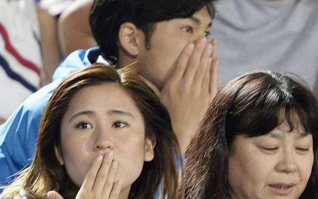 Japanese soccer fans react to a strong earthquake as they watch a J-League soccer match at BMW Stadium in Hiratsuka, southwest of Tokyo Saturday, May 30, 2015. (Munehide Someya/Kyodo News via AP)