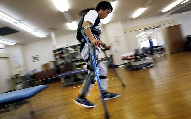 Yuichi Imahata walks using a robotic exoskeleton called ReWalk at Kanagawa Rehabilitation Center in Atgugi, Japan on April 17, 2015. Imahata, 31, has been using a wheelchair to get around for seven years after a serious spinal-cord injury suffered in an accidental fall while working for a transport company.  (Photo credit: Shuji Kajiyama/AP)