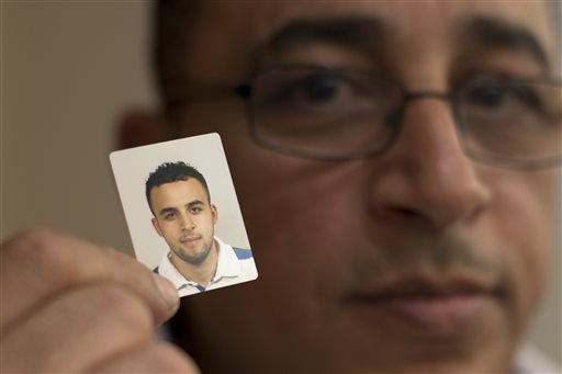 Mohamed Nidalha poses with a passport photo of his son Reda during an interview on Friday, May 15, 2015, in Leiden, Netherlands. The 20-year-old Reda, who grew up liking girls and going to discos, suddenly changed, thanks to a toxic cocktail of online propaganda and covert contact with extremists in Belgium, one of Europe's hotspots for Islamic radicals, and eventually traveled to Syria. (AP Photo/Peter Dejong)