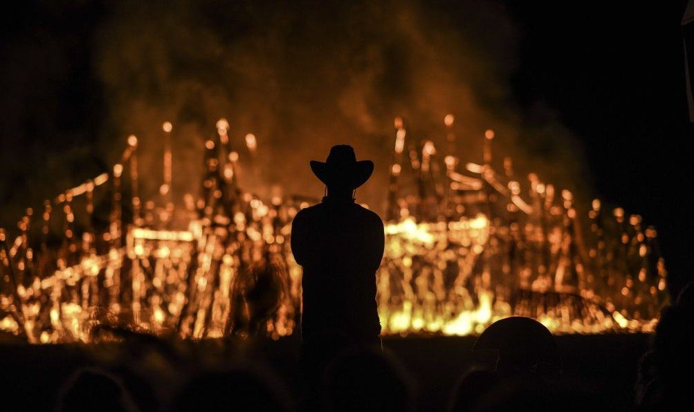Midburn participant watches an installation burn at the second annual festival modeled after America's Burning Man on May 24, 2015. (Photo credit: Ben Kelmer/Flash90)
