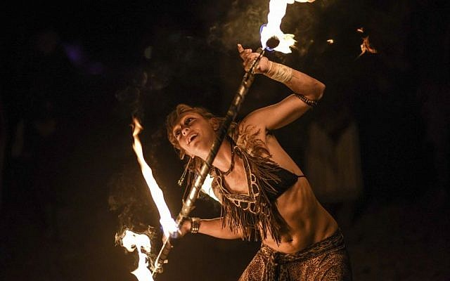 A Midburn participant twirls flaming baton at the second annual festival modeled after America's Burning Man on May 24, 2015. (Ben Kelmer/Flash90)