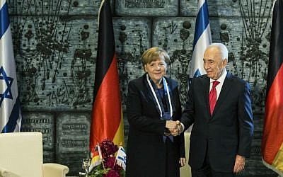 German Chancellor Angela Merkel received the Presidential Medal, Israel's highest honor, from then President Shimon Peres in Jerusalem, Feb. 25, 2014. (Ilia Yefimovich/Getty Images/ via JTA)