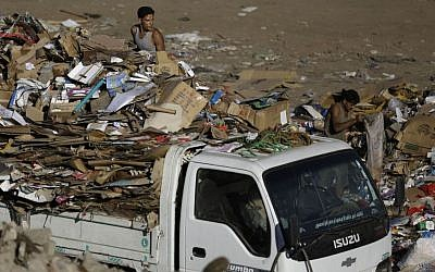 In this Oct. 23, 2014 file photo, Egyptian garbage collectors carry paper on a truck as they sift through garbage in Cairo, Egypt. (Photo credit: AP/Hassan Ammar, File)