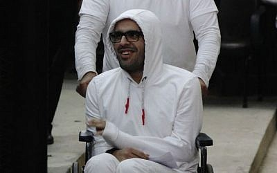 Mohammed Soltan is pushed in a wheelchair during a court appearance in Cairo, Egypt, March 9, 2015. (AP/Heba Elkholy)