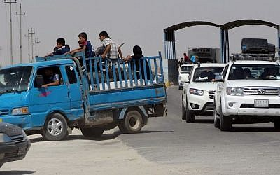 In this Monday, May 18, 2015 photo, civilians fleeing their hometown of Ramadi, Iraq, pull over their truck at a police checkpoint as they drive through Habaniyah town, 80 kilometers (50 miles) west of Baghdad. (AP)