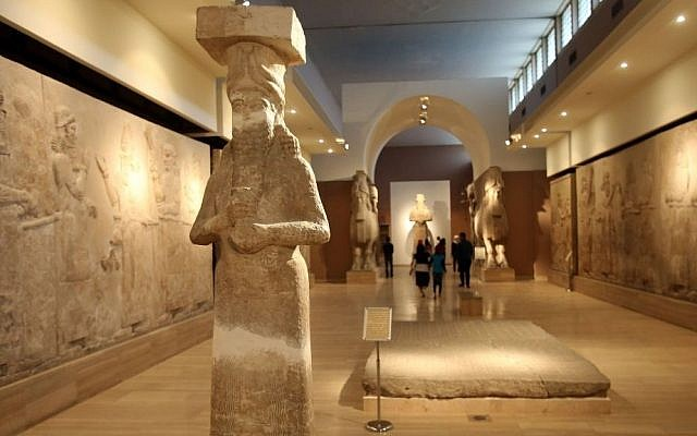 People observe ancient artifacts at the Iraqi National Museum on March 15, 2015 after its reopening in the wake of the recent destruction of Assyrian archaeological sites by the Islamic State group in Mosul, as they visit the museum in Baghdad. (photo credit: Karim Kadim/ AP)