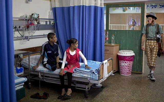 Palestinian siblings Ahmed, right, and Hadeel Hamdan, center, watch medical clown who goes by the name 'Juhl' at the Rambam Health Care Campus in Haifa, Israel, May 13, 2015 (AP/Ariel Schalit)
