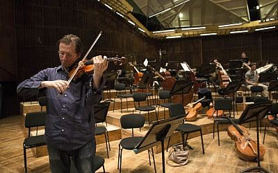 David Radzynski an American-Israeli concertmaster of the Israel Philharmonic Orchestra, plays during a rehearsal in Tel Aviv on May 3, 2015. Radzynski is still getting used to his first job out of college as the new concertmaster of the Israel Philharmonic Orchestra - and to being one of the youngest violinists to lead a major world orchestra today. (photo credit: AP Photo/Tsafrir Abayov)
