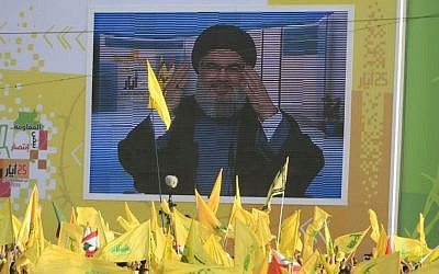 "Hezbollah leader Sheikh Hassan Nasrallah delivers a speech shown on a screen during a rally commemorating ""Liberation Day,"" which marks the withdrawal of the Israeli army from southern Lebanon in 2000, in the southern town of Nabatiyeh, Lebanon, Sunday, May 24, 2015.  (AP Photo/Mohammed Zaatari)"